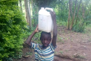 The Water Project: Nambatsa Community, Odera Spring -  Young Boy Carrying Home Water From The Unprotected Hole