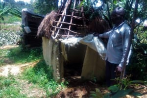 The Water Project: Handidi Community, Chisembe Spring -  Mr Edgera Water User Stands Beside His Latrine