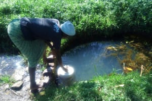The Water Project:  Dunking Jerrycan Into Spring