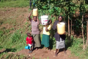 The Water Project: Musiachi Community, Thomas Spring -  Lifting Jerrycans Filled With Water Onto Heads