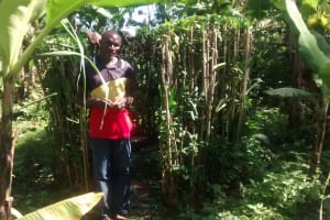 The Water Project: Musiachi Community, Thomas Spring -  Man Stands With Improvized Latrine