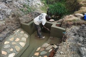 The Water Project: Futsi Fuvili Community, Simeon Shimaka Spring -  Paving Cement Walls