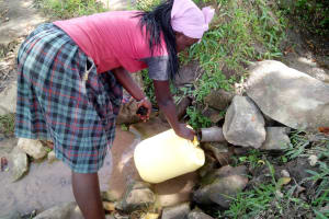The Water Project: Indete Community, Udi Spring -  Filling Jerrycan At Source