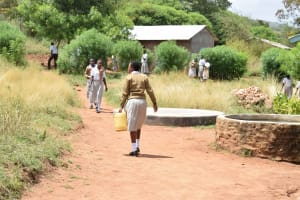The Water Project: Kithoni Secondary School -  Girl Walks With Collected Water