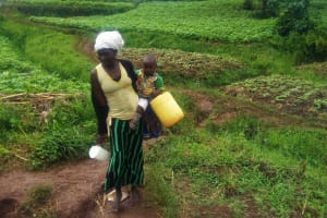 The Water Project: Emulakha Community, Alukoye Spring -  Mary Indiangala Carrying Her Water Container And Her Child Heading To The Unprotected Water Source