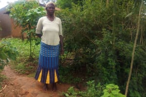 The Water Project: Emulakha Community, Alukoye Spring -  Mrs Caroli Poses Beside The Hole In The Ground That Acts As Her Latrine