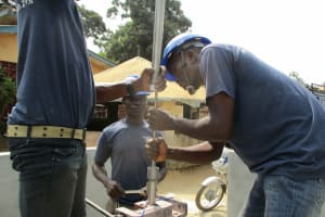The Water Project: Tholmosor Community, Alpha Dabola Road -  Fixing The Pipe