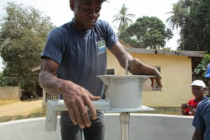 The Water Project: Tholmosor Community, Alpha Dabola Road -  Installing The Pipe