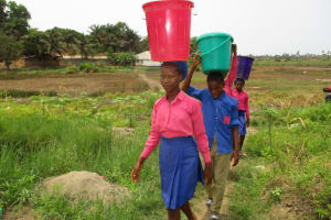 The Water Project: St. John RC Primary School -  Students Carrying Water