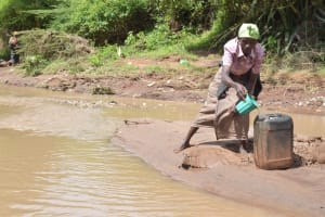 The Water Project: Kala Community -  Pouring Water Into Larger Container