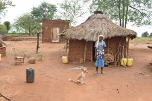 The Water Project: Ikuusya Community A -  Standing Outside Of Kitchen With Dog