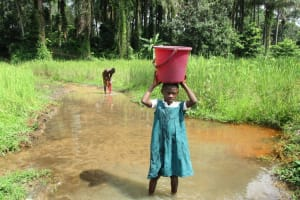 The Water Project: DEC Mathem Primary School -  Girl Carrying Water