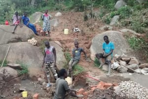 The Water Project: Chandolo Community, Joseph Ingara Spring -  Workers With Gathered Materials For Spring Protection