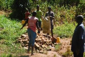 The Water Project: Jivovoli Community, Wamunala Spring -  Community Contributes To Spring Protection