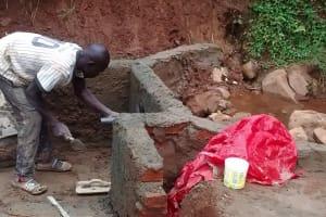 The Water Project: Jivovoli Community, Gideon Asonga Spring -  Inserting Pipe Into Spring