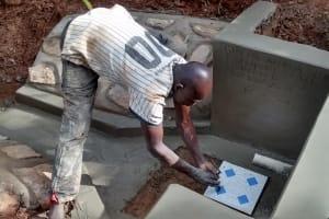 The Water Project: Jivovoli Community, Gideon Asonga Spring -  Laying Tile