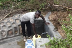 The Water Project: Masera Community, Ernest Mumbo Spring -  Collecting Water From Protected Spring