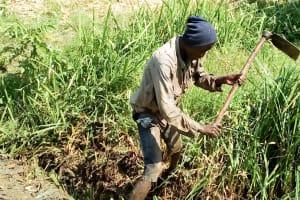 The Water Project: Musango Community, Jared Lukoko Spring -  Community Member Digging Drainage
