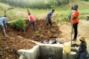 The Water Project: Musango Community, Jared Lukoko Spring -  Planting Grass Behind Spring