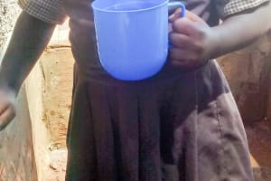 The Water Project: Mwanzo Primary School -  Little Nulin Kayeshe Shares Her Joy By Smiling After Trying Water From The Tank
