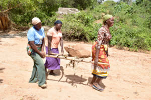 The Water Project: Ilandi Community A -  Transporting A Heavy Stone To The Dam