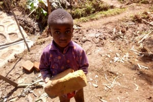 The Water Project: Irumbi Community, Shatsala Spring -  A Little Boy Delivering A Brick To The Artisan