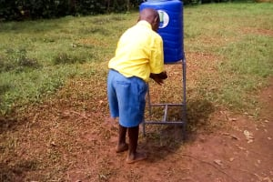 The Water Project: Eshilibo Primary School -  Student Using New Handwashing Station