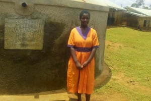 The Water Project: Essunza Primary School -  Hellen Angoya In Front Of The Tank