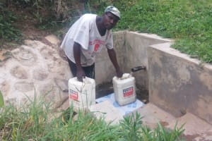 The Water Project: Bushevo Community, David Enani Spring -  Moses Enani Collecting Water