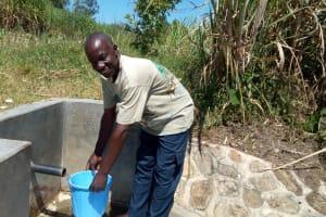 The Water Project: Chegulo Community, Shakava Spring -  Tom Shakava Collecting Water