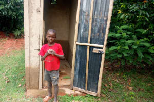 The Water Project: Timbito Community, Atechere Spring -  A Boy Poses In Front Of A Latrine Constructed By A Sanplat