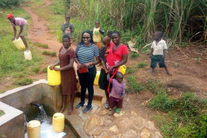 The Water Project: Timbito Community, Atechere Spring -  Field Officer Christine Center Poses For A Picture With Community Members At The Spring