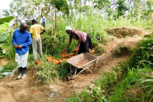 The Water Project: Chegulo Community, Werabunuka Spring -  Carrying Bricks To The Artisan