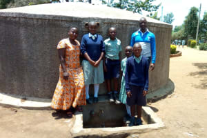 The Water Project: Shibale Primary School -  Field Officer Betty Majani Poses With Students At The Tank