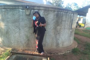 The Water Project: Iyenga Primary School -  Field Officer Jacklyne Chelagat Drinks From The Tank