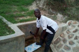 The Water Project: Futsi Fuvili Community, Shikanga Spring -  A Man Collects Water From The Spring