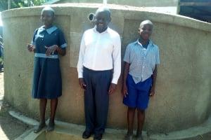 The Water Project: Namalenge Primary School -  Headteacher Alex Ywaya Posing With Lvenda Adeya And Owen Wanaami At The Tank