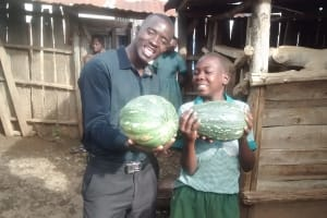 The Water Project: Ebusiratsi Special Primary School -  Field Officer Erick Wagaka And Dan Carrying Pumkin Fruit Harvested From The School Farm