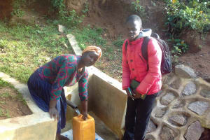 The Water Project: Gidagadi Community, Anusu Spring -  Field Officer Samuel Simidi With Lydia Sayo At The Spring