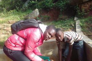 The Water Project: Gidagadi Community, Anusu Spring -  Field Officer Samuel Simidi And Brighton Mudonyi
