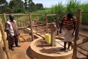 The Water Project: Rubona Kyagaitani Community -  Community Members Using The Water Point