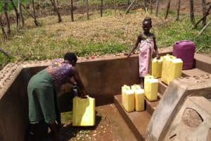 The Water Project: Rwempisi-Amanga Community -  Filling Containers With Spring Water