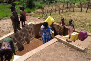 The Water Project: Rwempisi-Amanga Community -  Lifting Filled Container Of Water To Carry Home