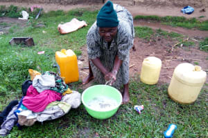 The Water Project: Bukhakunga Community, Ngovilo Spring -  Using Water To Wash Clothes