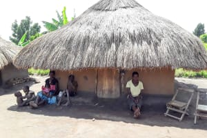The Water Project: Karagalya Kawanga Community -  Nyamungu Grace And Her Children Seated Outside Of Her Hut