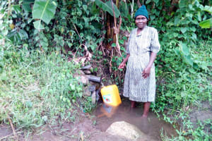 The Water Project: Bukhakunga Community, Ngovilo Spring -  Mrs Ngovilo Fetching Water