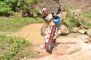 The Water Project: Ivumbu Community -  Hoisting The Filled Container Onto Her Back To Carry Home