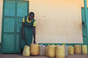 The Water Project: Kakunike Primary School -  Student Fetches Water From Containers In Front Of Classroom