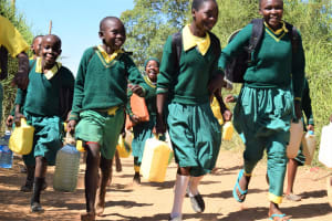 The Water Project: Kakunike Primary School -  Students Carrying Water