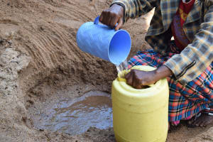 The Water Project: Murwana Primary School -  Filling Plastic Container With Water From The Scoop Hole